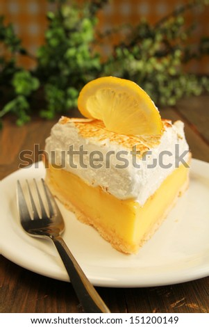 Lemon pie with meringue and fork on a wooden table - stock photo