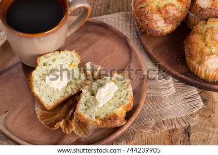 Lemon poppy seed muffins and cup of coffee on a wooden plate