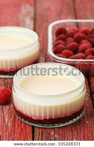 Lemon possets with raspberries on a red wooden background - stock photo