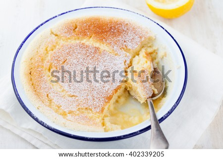 Lemon pudding cake with fresh lemons on a white wooden background Copy space  - stock photo
