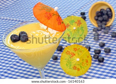 Lemon pudding with blueberries in festive setting with paper umbrellas. - stock photo