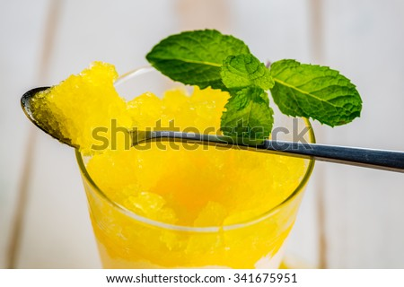 Lemon refreshing dessert in glass decorated with lemon and mint on white wood table