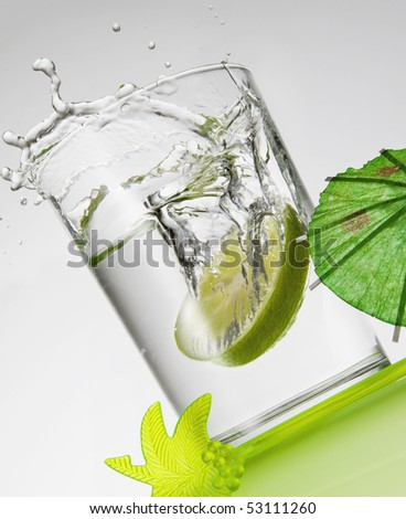 Lemon slice falls in a glass of water on a green table - Splash - stock photo