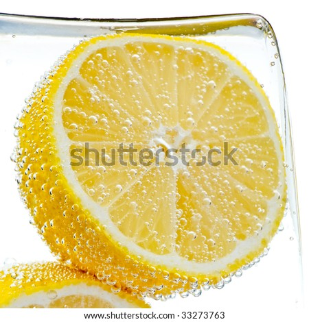 Lemon slice in water with bubbles - stock photo