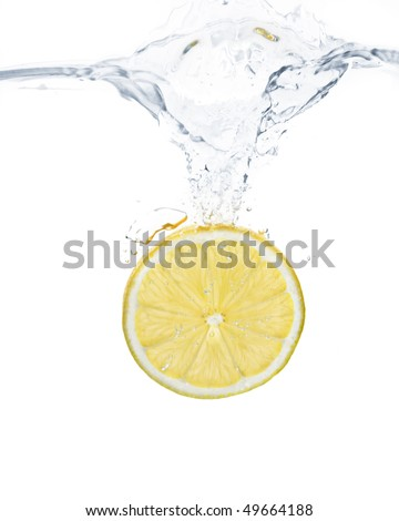 lemon slice splashing into water with white background - stock photo