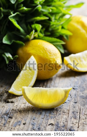 Lemon slices and spearmint on rustic wooden table - stock photo