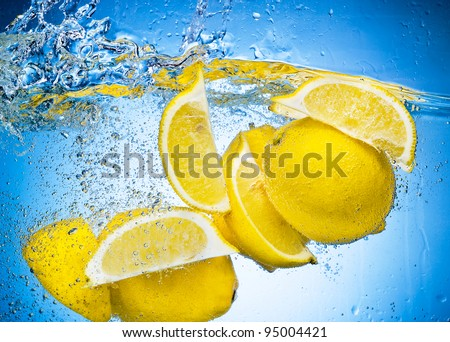 Lemon Slices falling deeply under water with a big splash on blue background - stock photo