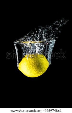 Lemon slices falling into the water close-up, macro, splash, bubbles, isolated on black background - stock photo