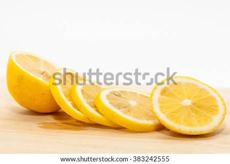 Lemon slices on wooden cutting board - stock photo