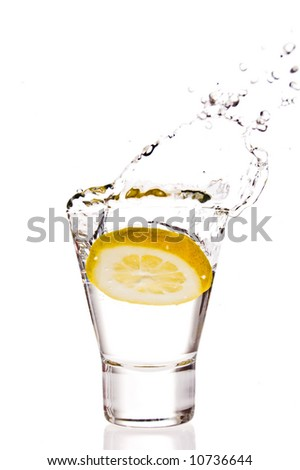 Lemon splashing into martini glass