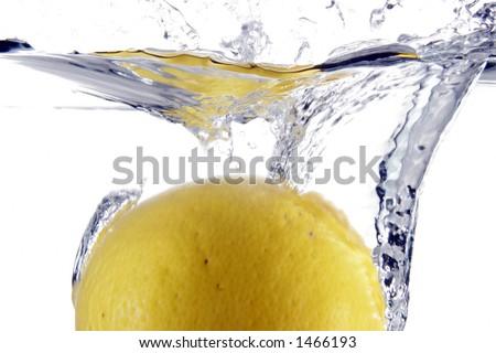 Lemon splashing into water - stock photo