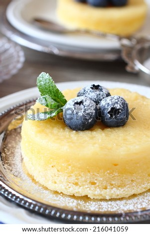 Lemon Sponge Souffle served with berries on plate - stock photo