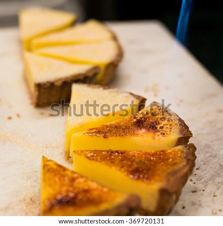 Lemon tart being torched to create a brulee.