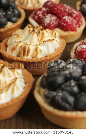 Lemon tarts and fruity tarts on a display - stock photo