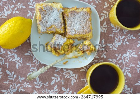 Lemon tarts on a plate, yellow cups and raw lemon on patterned l - stock photo
