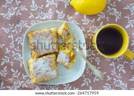 Lemon tarts powdered with sugar, yellow mug with tea and lemon f - stock photo