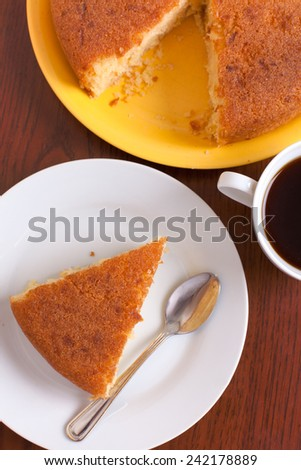 Lemon tasty homemade cake and coffee cup on a brown wood table