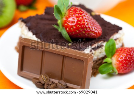 lemon tea,chocolate, kiwi,cake and strawberries lying on the orange fabric - stock photo