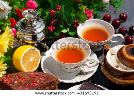 Lemon tea in two pairs of tea in the sun. Samovar creates comfort. Sponge cake and pieces of sugar in the sugar bowl making sweet tea drinking. - stock photo