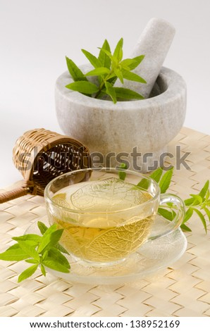 Lemon verbena Herbal Tea in a glass cup. Aloysia citriodora.  Naturopathy. White Background. Focus on foreground.