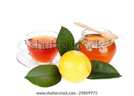 Lemon with green leaves, pot of honey and cup of tea on a white background