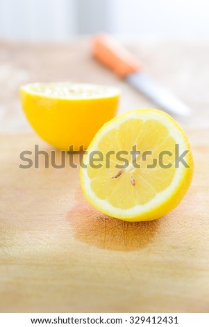 Lemon with knife on cutting board