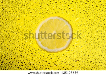 Lemon with water drops isolated on yellow background. - stock photo