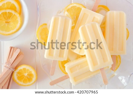 Lemon yogurt popsicles in a transparent serving bowl against a white wood background - stock photo