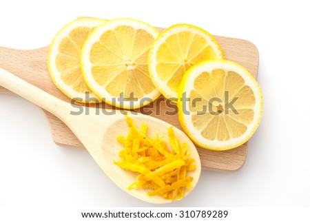 Lemon zest and sliced lemons on a cutting boards, ingredients for a dessert - stock photo