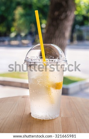 Lemonade,  a refreshing drink in a plastic cup. City cafe,  street background. - stock photo