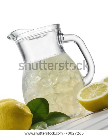 Lemonade and ice in a glass jar with lemons and leaves on withe background - stock photo