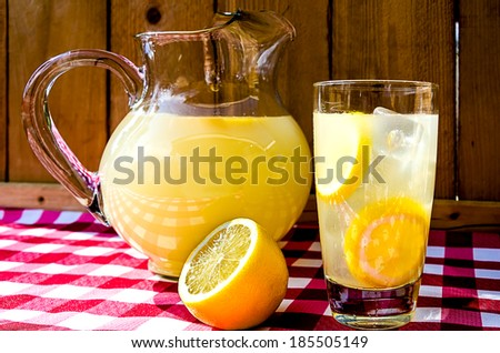 Lemonade and pitcher with sliced lemons on red gingham table cloth.  - stock photo