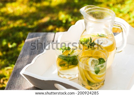 Lemonade drink in the glasses and jug on the white tray - stock photo