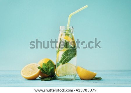 Lemonade drink of soda water, lemon and mint leaves in jar on turquoise background - stock photo
