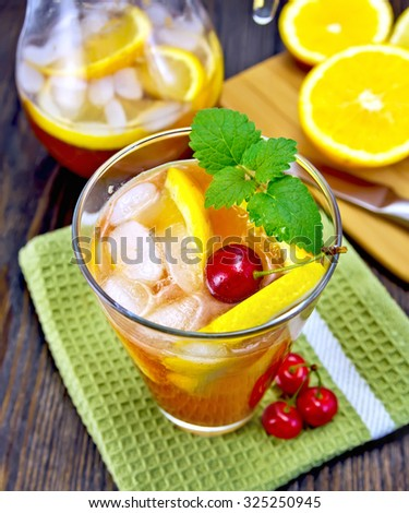 Lemonade in a glass and a jug with cherry, lemon and orange, mint, green napkin with fruit on the background of dark wooden board