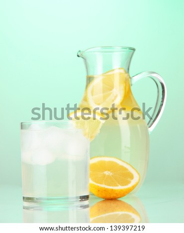 Lemonade in pitcher and glass on green background