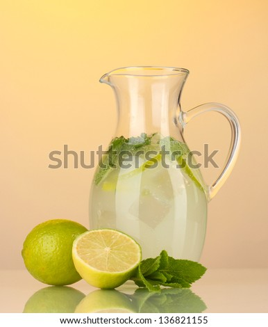 Lemonade in pitcher on yellow background