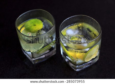Lemonade served on a dark marble bar top garnished with a lime view 4 - stock photo