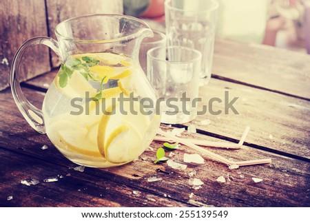 Lemonade with fresh lemon on wooden background - stock photo