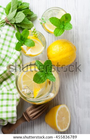 Lemonade with lemon, mint and ice on wooden table. Top view