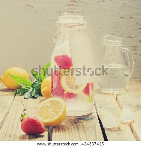 lemonade with lemon, strawberries and mint on wooden background. rustic style. blank paper tag with space for text. toned image - stock photo