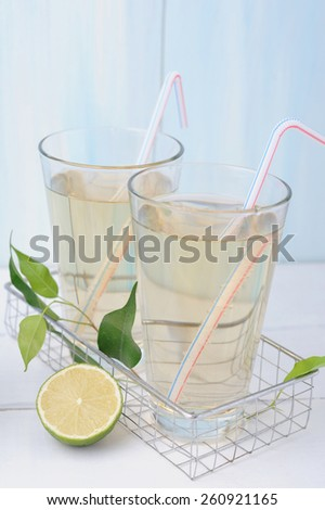 Lemonade with lemons and fresh wet leaves - stock photo