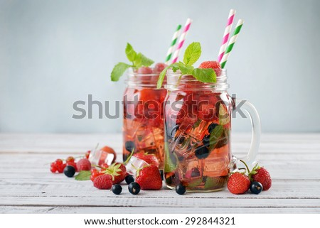 Lemonade with summer berries in glass jar with handle on wooden background - stock photo