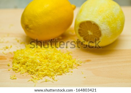 Lemons and lemon peel on wooden board with grater