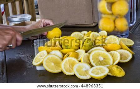 Lemons being slice in preparations for lemon crush drink. - stock photo