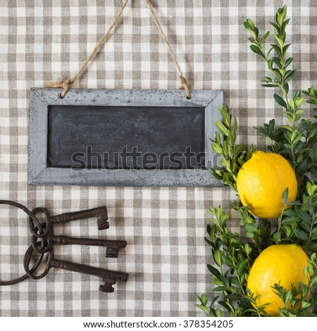 Lemons, green branches, old keys and chalkboard on the background of checkered textile