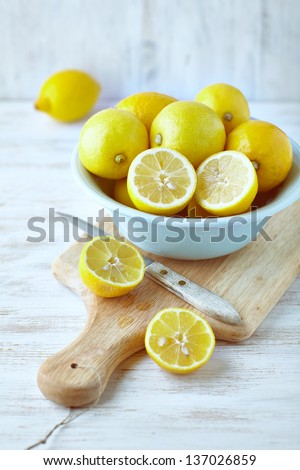 Lemons in a bowl; whole and halved - stock photo