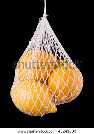 Lemons in a net bag against a black background - stock photo