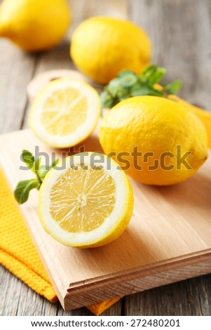 Lemons on cutting board on grey wooden background - stock photo