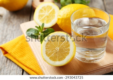 Lemons on cutting board with glass of water on grey wooden background - stock photo